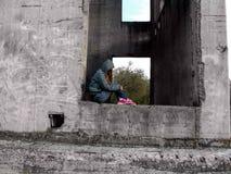 Un adolescente en una capilla sin una cara se sienta en un agujero rectangular de un muro de cemento Foto de archivo