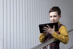 Un adolescente en una chaqueta a cuadros y una camisa amarilla mira la tableta irritablemente mientras que juega o trabaja Imagen de archivo