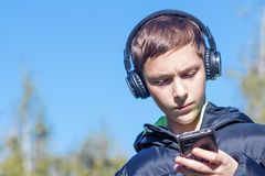 Un adolescente en una chaqueta negra con los auriculares mira seriamente el smartphone en el parque en un fondo del cielo azul Foto de archivo libre de regalías