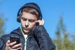 Un adolescente en una chaqueta negra en un día soleado del otoño mira el teléfono y escucha la música en los auriculares Imágenes de archivo libres de regalías