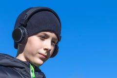 Un adolescente en una chaqueta y un sombrero negros está llevando a cabo su mano en los auriculares y está escuchando la música e Imagen de archivo