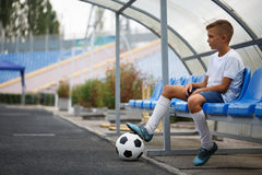 Un adolescente en una sentada uniforme del fútbol en un banco azul en un fondo del estadio Deporte, fútbol y concepto saludable Imágenes de archivo libres de regalías