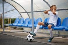 Un adolescente en una sentada uniforme del fútbol en un banco azul en un fondo del estadio Deporte, fútbol y concepto saludable Fotografía de archivo