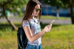 Un adolescente en verano en ropa del dril de algodón Detrás de la mochila en gafas de sol En sus manos sostiene un smartphone Con Fotos de archivo libres de regalías
