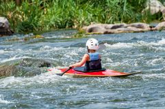 Un adolescente entrena en el arte de kayaking Barco en rápidos ásperos del río Contratan al niño hábilmente a transportar en bals Foto de archivo