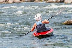 Un adolescente entrena en el arte de kayaking Barco en rápidos ásperos del río Contratan al niño hábilmente a transportar en bals Imagenes de archivo