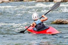 Un adolescente entrena en el arte de kayaking Barco en rápidos ásperos del río Contratan al niño hábilmente a transportar en bals Imagen de archivo libre de regalías