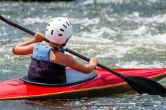 Un adolescente entrena en el arte de kayaking Barco en rápidos ásperos del río Contratan al niño hábilmente a transportar en bals Imágenes de archivo libres de regalías