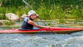 Un adolescente entrena en el arte de kayaking Barco en rápidos ásperos del río Contratan al niño hábilmente a transportar en bals Fotos de archivo libres de regalías