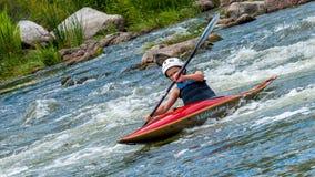 Un adolescente entrena en el arte de kayaking Barco en rápidos ásperos del río Contratan al niño hábilmente a transportar en bals Fotografía de archivo libre de regalías