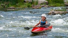 Un adolescente entrena en el arte de kayaking Barco en rápidos ásperos del río Contratan al niño hábilmente a transportar en bals Foto de archivo libre de regalías