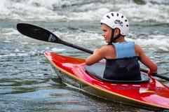 Un adolescente entrena en el arte de kayaking Barco en rápidos ásperos del río Contratan al niño hábilmente a transportar en bals Fotos de archivo
