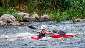 Un adolescente entrena en el arte de kayaking Barco en rápidos ásperos del río Contratan al niño hábilmente a transportar en bals Fotografía de archivo
