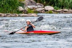 Un adolescente entrena en el arte de kayaking Barco en rápidos ásperos del río Contratan al niño hábilmente a transportar en bals Imagen de archivo