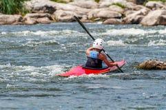 Un adolescente entrena en el arte de kayaking Eslalom en rápidos ásperos del río Contratan al niño hábilmente a transportar en ba Foto de archivo