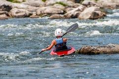 Un adolescente entrena en el arte de kayaking Eslalom en rápidos ásperos del río Contratan al niño hábilmente a transportar en ba Imagenes de archivo