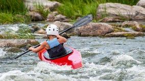Un adolescente entrena en el arte de kayaking Eslalom en rápidos ásperos del río Contratan al niño hábilmente a transportar en ba Fotos de archivo