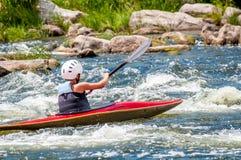Un adolescente entrena en el arte de kayaking Eslalom en rápidos ásperos del río Contratan al niño hábilmente a transportar en ba Imagen de archivo