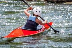 Un adolescente entrena en el arte de kayaking Eslalom en rápidos ásperos del río Contratan al niño hábilmente a transportar en ba Foto de archivo libre de regalías