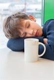 Un adolescente está durmiendo en café Imagen de archivo libre de regalías