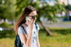 Un adolescente está hablando en el teléfono En el verano en el parque en naturaleza Morenita en gafas de sol Una colegiala despué Imagen de archivo