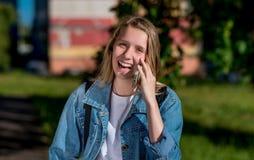 Un adolescente está hablando en un smartphone Sonrisa y risa felices En el verano en el parque en aire fresco emocional Fotografía de archivo libre de regalías