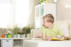Un adolescente está leyendo un libro Imagen de archivo libre de regalías