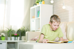 Un adolescente está leyendo un libro Foto de archivo libre de regalías