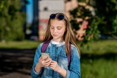 Un adolescente está llevando a cabo las manos con un teléfono La sonrisa feliz está escribiendo en redes sociales En verano en el Imágenes de archivo libres de regalías