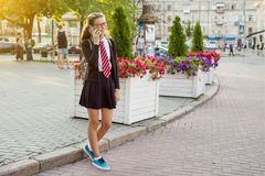 Un adolescente - estudiante de la High School secundaria en una calle de la ciudad que habla encendido Imagen de archivo
