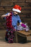 Un adolescente europeo tipico in un cappello di Santa Claus esamina un petto di legno aperto ed estrae le decorazioni di Natale  fotografie stock
