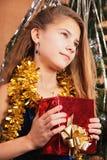 Un adolescente fantasea sobre el contenido de su regalo de la Navidad Fotos de archivo