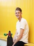 Un adolescente feliz con un monopatín en un fondo amarillo Un exterior relajante casual, despreocupado, bonito, de risa del indiv Fotografía de archivo