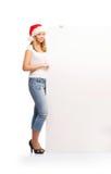Un adolescente feliz en un sombrero de la Navidad que sostiene una bandera Foto de archivo