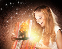 Un adolescente feliz que abre un regalo de Navidad Imagen de archivo libre de regalías