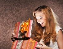 Un adolescente feliz que abre un regalo de Navidad Foto de archivo