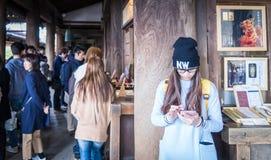 Un adolescente japonés está jugando con su teléfono celular en un templo Imagen de archivo