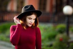 Un adolescente joven en una camisa y un sombrero negros Imagen de archivo