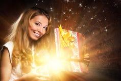 Un adolescente joven que abre un regalo de Navidad Foto de archivo libre de regalías