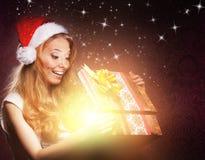 Un adolescente joven que abre un regalo de Navidad Fotografía de archivo