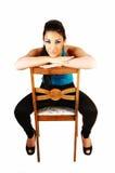 Muchacha que se sienta en silla. Imagen de archivo libre de regalías