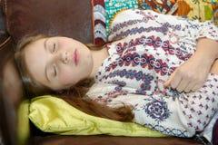 Un adolescente joven que tiene un dolor de estómago que duerme en el sofá Foto de archivo libre de regalías