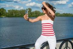 Un adolescente joven tira el vídeo en un smartphone para su channe Foto de archivo