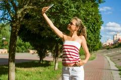Un adolescente joven tira el vídeo en un smartphone para su channe Imagen de archivo libre de regalías