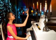Un adolescente juega un piano en una noche de la Navidad por luz de una vela Imagen de archivo libre de regalías
