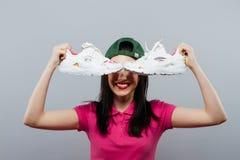 Un adolescente lindo en su falda que soporta sus zapatos con una expresión confusa en su cara fotografía de archivo