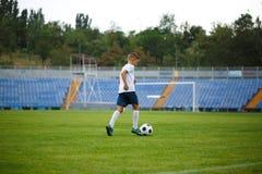 Un adolescente lindo que golpea la bola del fútbol en un fondo del estadio Niños que entrenan a fútbol Concepto de los deportes Fotografía de archivo