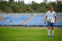 Un adolescente lindo que golpea la bola del fútbol en un fondo del estadio Niños que entrenan a fútbol Concepto de los deportes Foto de archivo