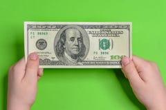Un adolescente lleva a cabo cientos dólares con dos manos en un fondo verde Imagen de archivo libre de regalías