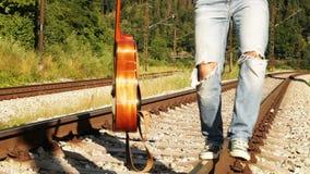 Un adolescente masculino camina equilibrando a lo largo del ferrocarril con la guitarra metrajes